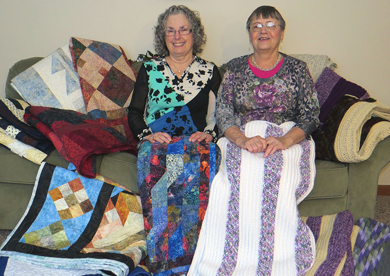 (Caption) Nancy Berndtson, mother of owners Sara Nadeau and Jason Berndtson, and Marie Nadeau, mother of owner Al Nadeau, working on resident Welcome Blankets and Quilts for the Grand Opening in the fall of 2015.